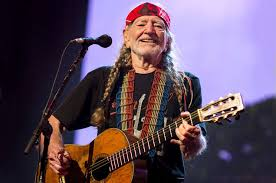 Country music star WIllie Nelson playing his guitar.