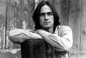 James Taylor, with his arms resting on a tree stump.