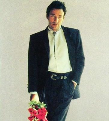 Bruce Springsteen, in a black suit holding a bouquet of red flowers.