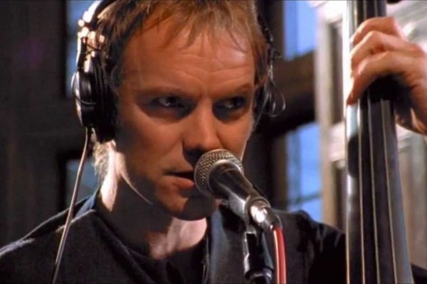 Sting, holding a bass as he sings into a microphone.