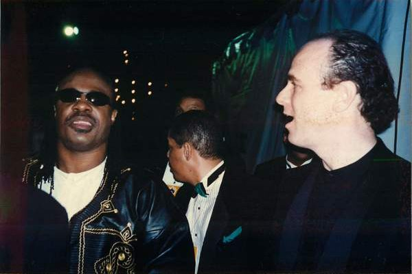 Stevie Wonder at the Grammys, with Dr. Weiss on the right hand side, looking excitedly.